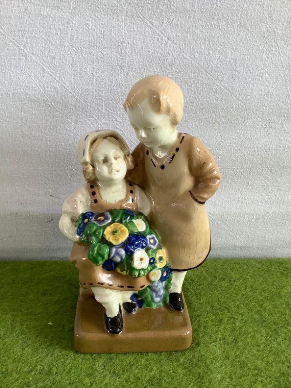 Beeldje van een jongen en een meisje met bloemen