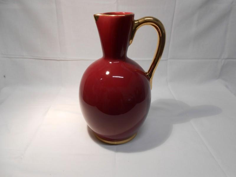 Rode vaas met goudkleurig handvat.
