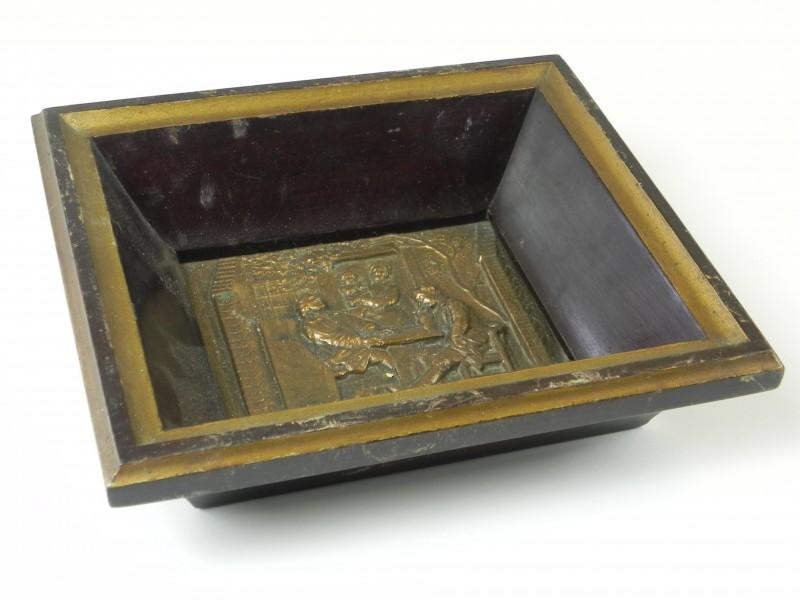 Metalen reliëf van huishoudelijk tafereel ingekaderd