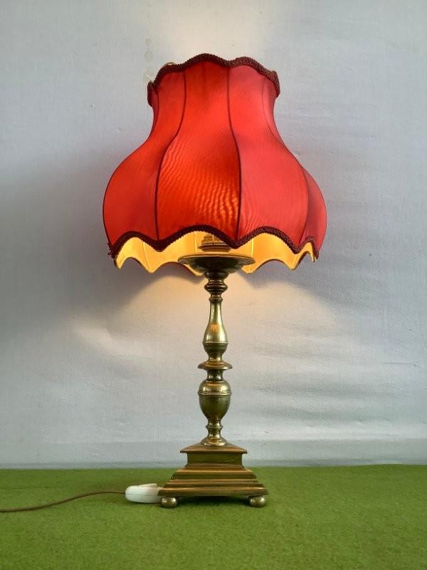 Oude koperen tafellamp met een rode kap