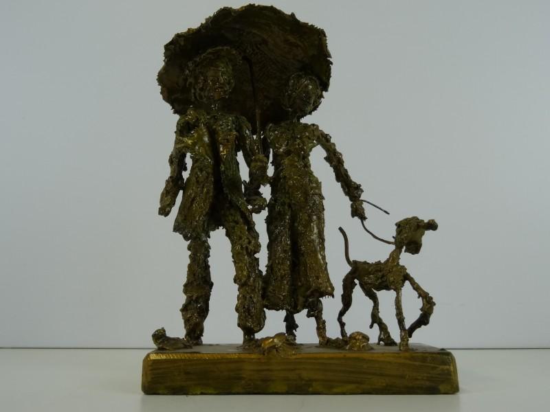 Duras: sculptuur van koppel onder paraplu met hond aan leiband 1980