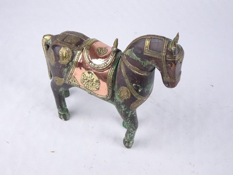 Paard met koperen en metalen versiering.