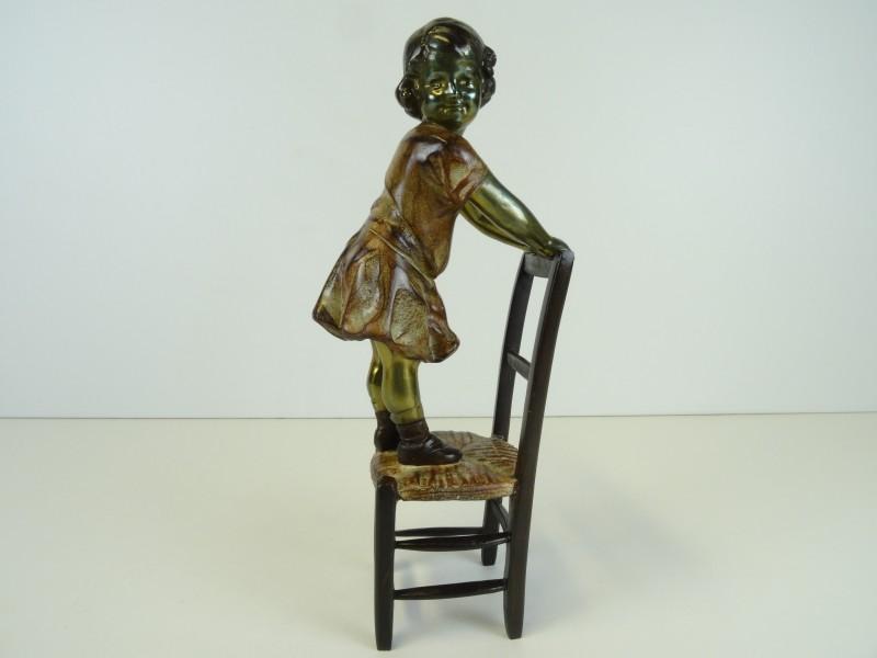 Beeldje van meisje staande op stoel