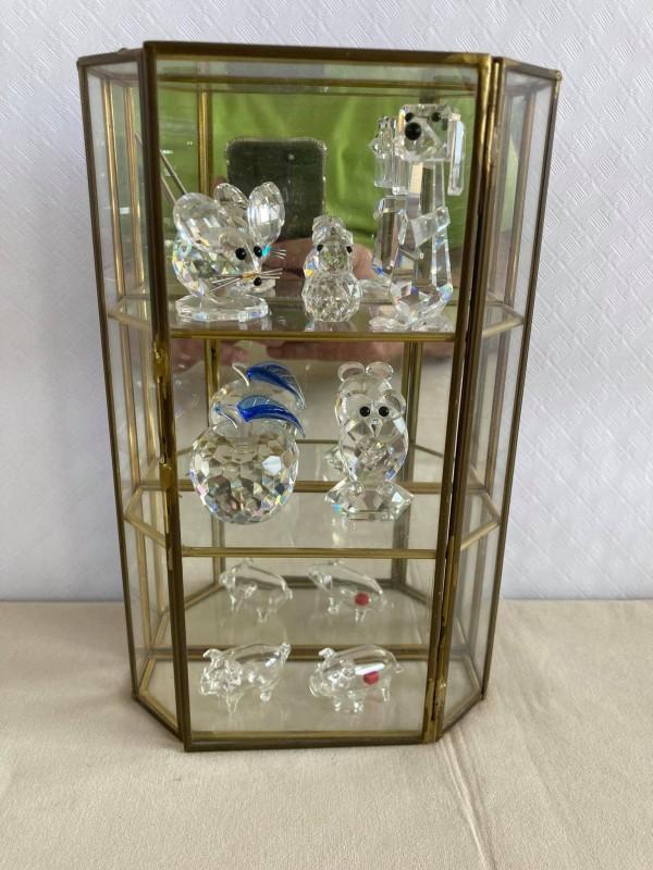 Vitrinekastje met glazen en kristallen beeldjes