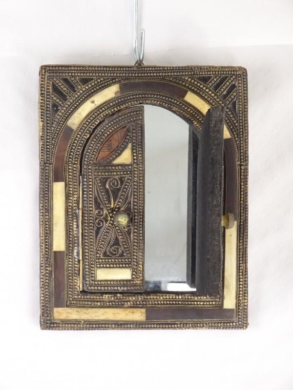 Kleine spiegel met deurtjes die kunnen open of dichtklappen.