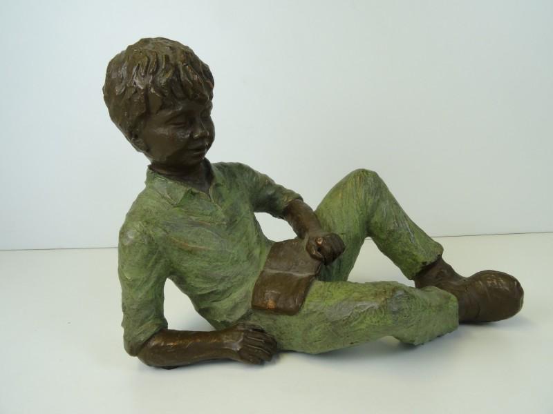 Bronzen tuinbeeld jongen die een boek leest, Gesigneerd