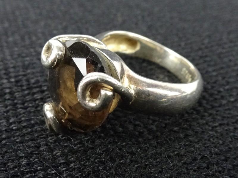 Zilveren ring met bruine steen.
