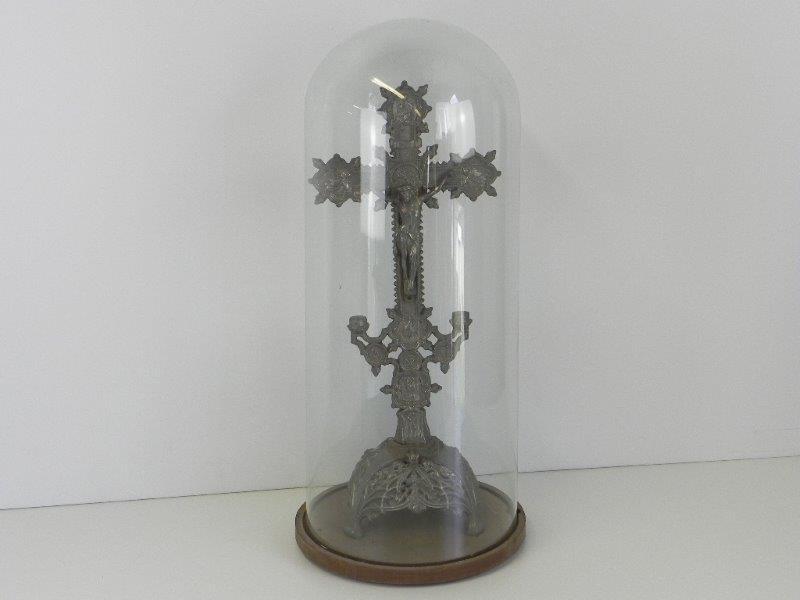 Een verzilverd metalen kruisbeeld onder glazen stolp.
